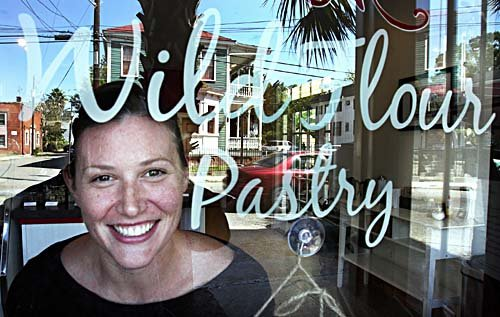 Lauren Mitterer looks through the window of her new shop on Spring Street, WildFlour Pastry